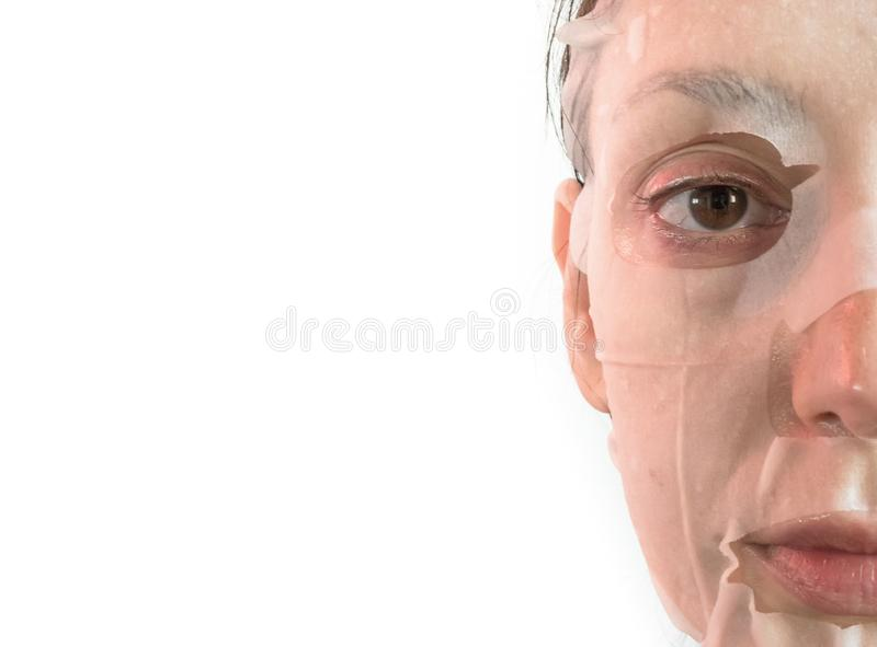 Young woman is applying a cosmetic tissue mask royalty free stock photography