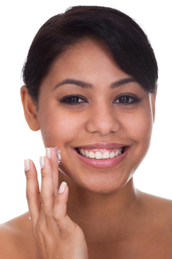 Young woman applying cream on her face stock image