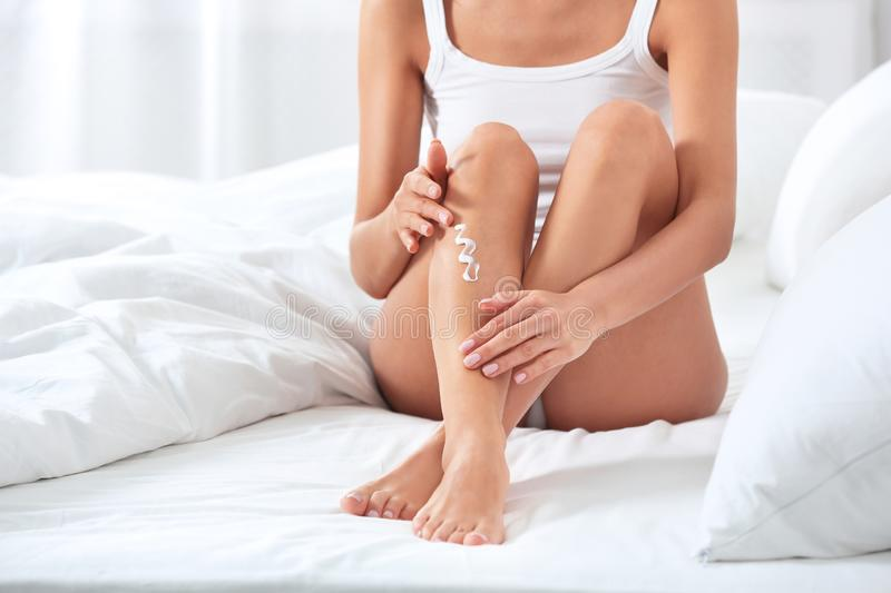 Young woman applying cream on her legs, closeup. Beauty and body care. Young woman applying cream on her legs indoors, closeup. Beauty and body care stock image