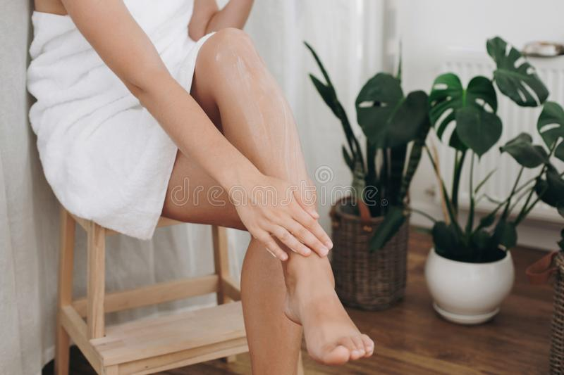Young woman applying cream on her legs after shaving in bathroom with green plants. Skin care and wellness concept. Girl hand with. Moisturizer cream smearing royalty free stock photos