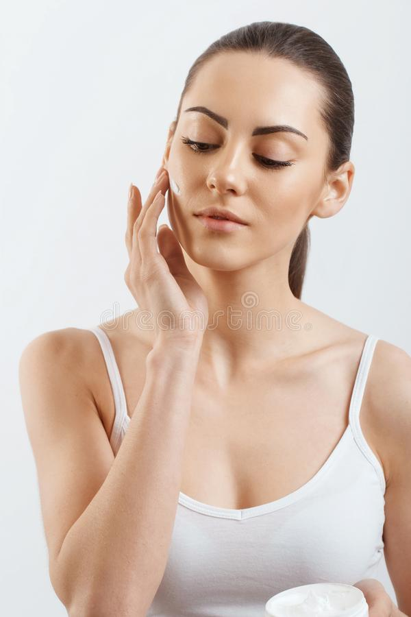 Beauty Young woman applying cream to her face. Skincare and cosmetics concept.Cosmetics. Woman face skin care. Young woman applying cream to her face. Skin care royalty free stock images