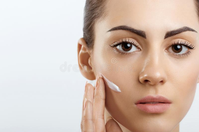 Beauty Young woman applying cream to her face. Skincare and cosmetics concept.Cosmetics. Woman face skin care. Young woman applying cream to her face. Skin care stock photo