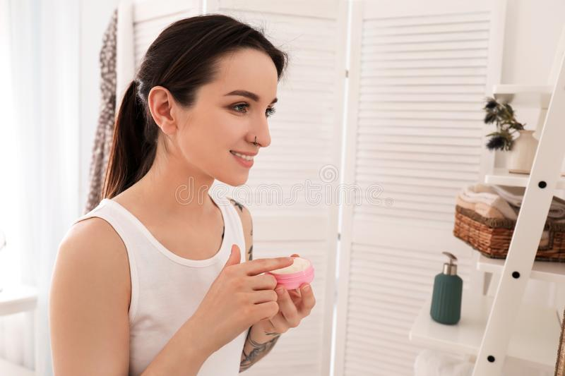 Young woman applying face cream in bathroom. Morning routine stock photography