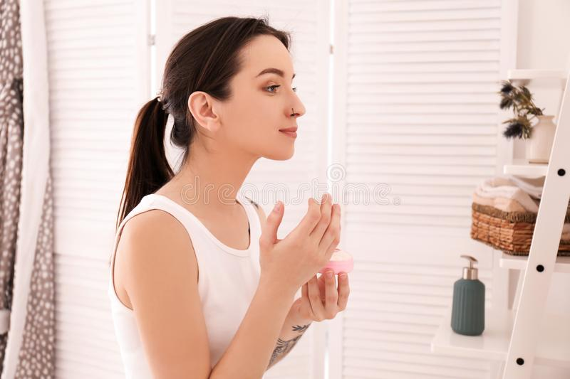 Young woman applying face cream in bathroom. Morning routine stock photo