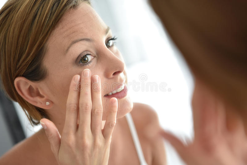 Young woman applying facial cream stock images