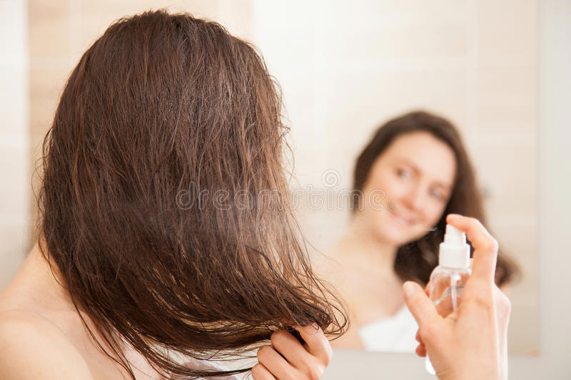 Young woman applying hair spray. Smiling young woman applying hair spray in front of a mirror; haircare concept royalty free stock photo