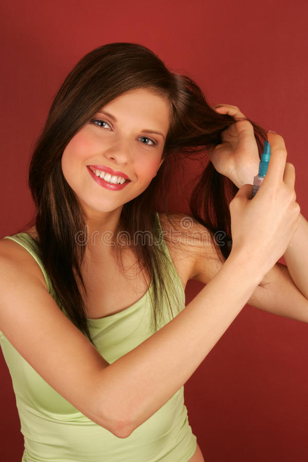 A young woman applying hairspray. royalty free stock photos