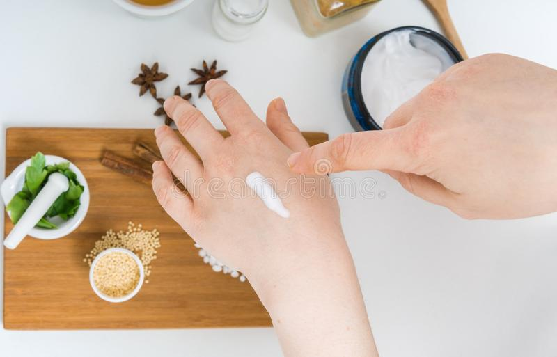 Young woman is applying homemade cosmetics on her skin.  royalty free stock image