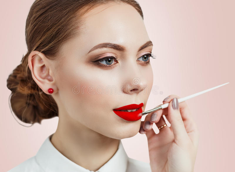Young woman applying lipstick with an applicator. Over pink background stock photography