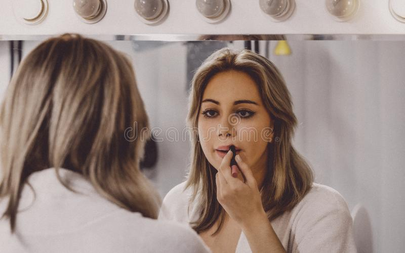 Young woman applying lipstick royalty free stock photos