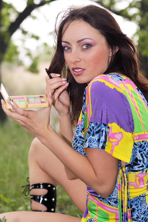 Young woman applying make up outdoors stock images