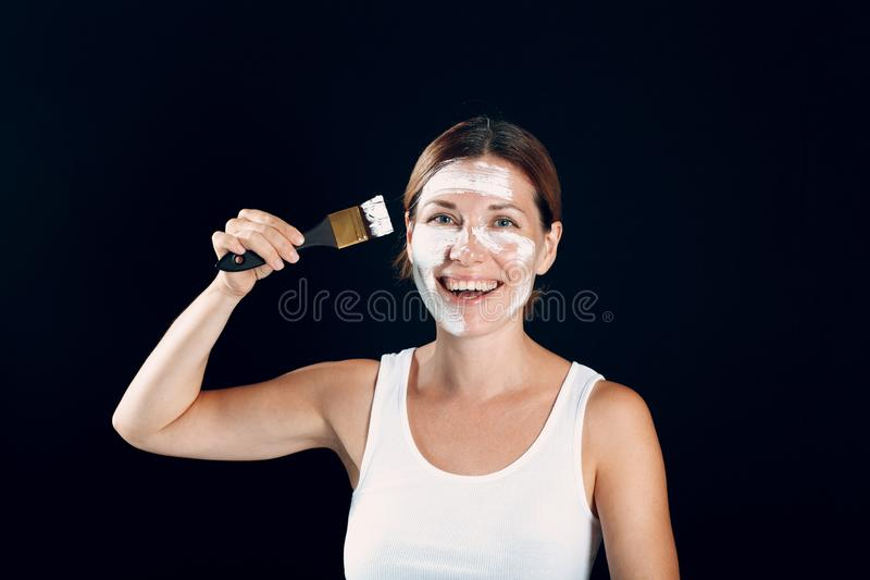 Young woman applying make-up, paints face with painting brush and makeup. How not to do make up concept stock photography