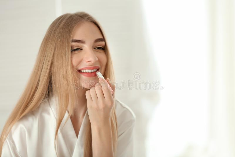 Young woman applying makeup in bathroom royalty free stock image