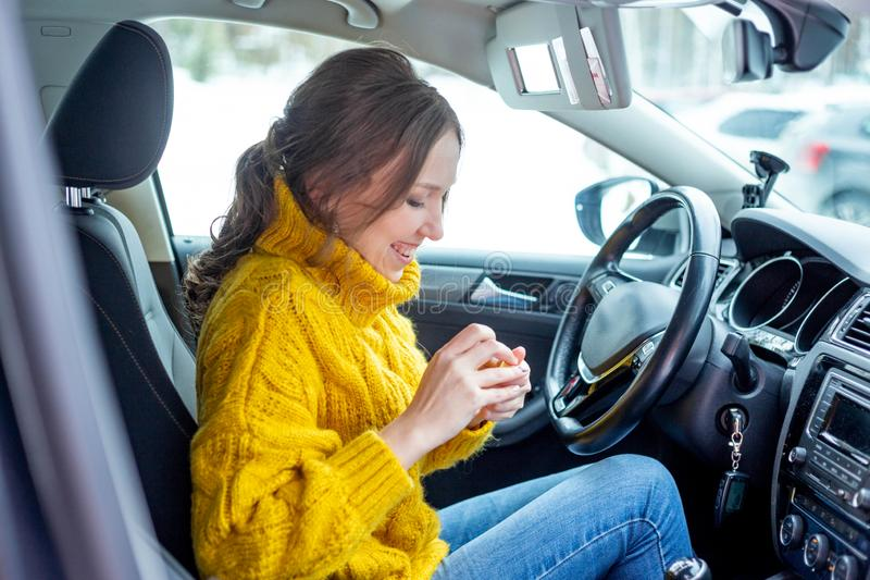 Young woman applying makeup in a car royalty free stock photography