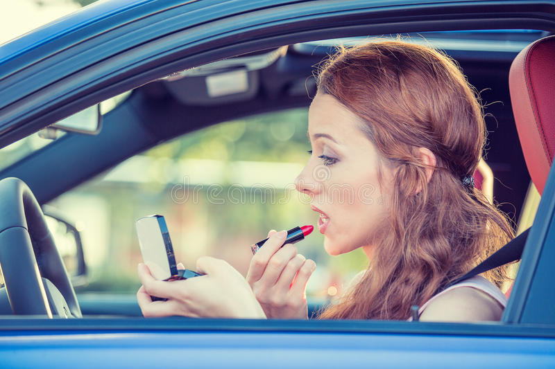 Young woman applying makeup while driving car. Side window view young woman applying makeup while driving car royalty free stock images