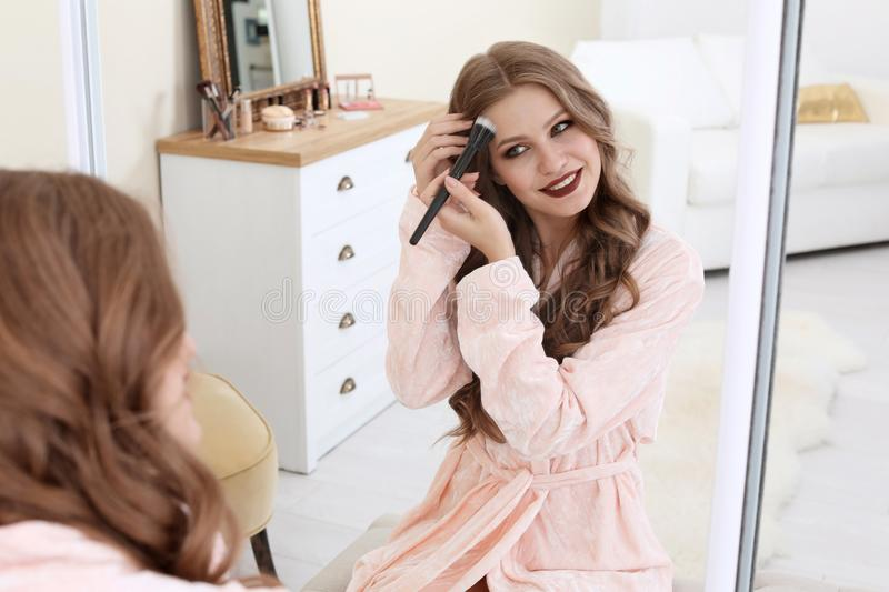 Young woman applying makeup near mirror in dressing room royalty free stock photo