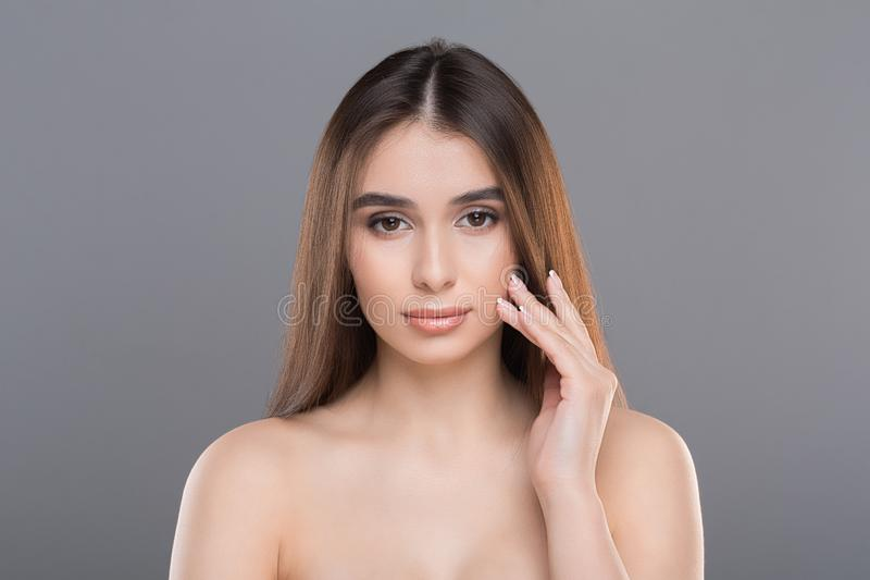 Young woman applying moisturizer cream on her pretty face. Young woman touching her cheek, applying moisturizer cream on her pretty face, grey studio background stock images