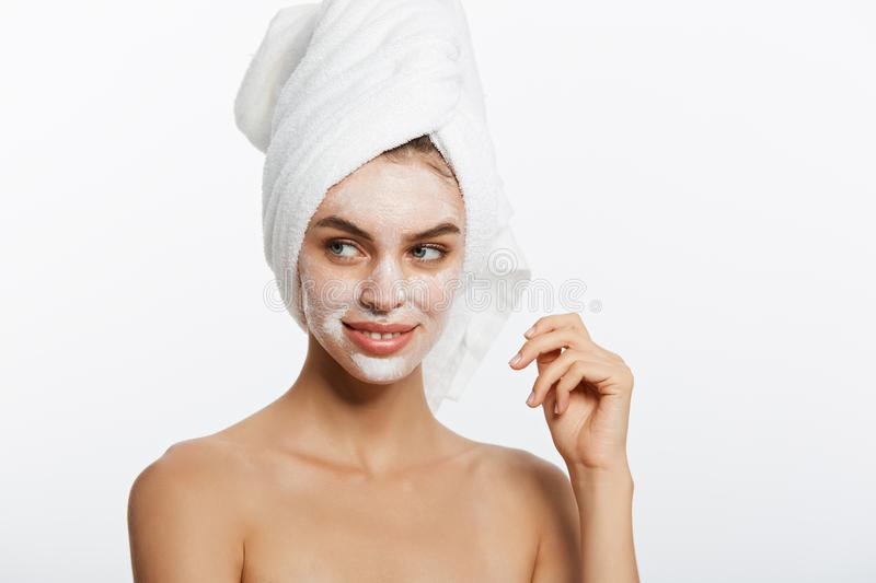 Young woman applying moisturizing cream on her face. Photo of woman in white bathrobe and towel on white background royalty free stock images