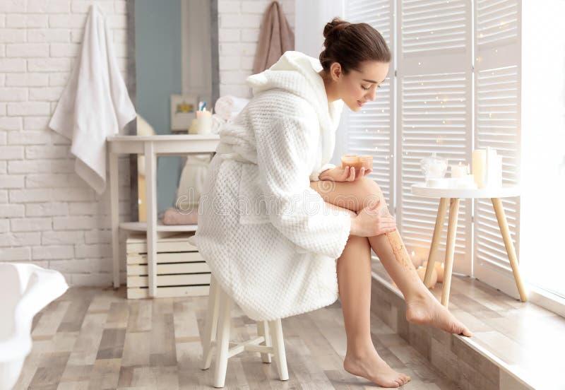 Young woman applying natural scrub onto her skin stock photos