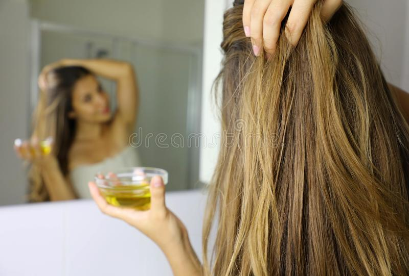 Young woman applying olive oil mask on hair in front of a mirror. Hair care concept. Focus on hair.  stock photography