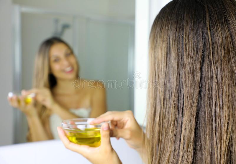 Young woman applying olive oil mask to hair in front of a mirror. Hair care concept. Focus on hair.  royalty free stock image