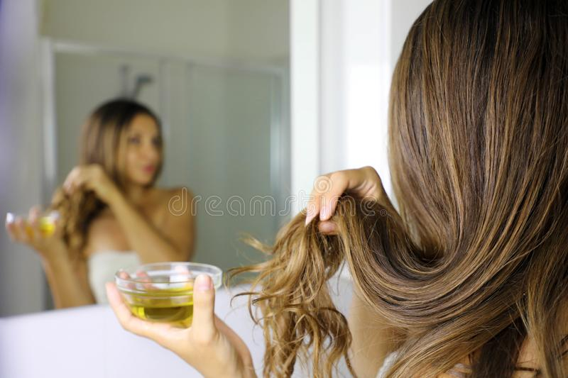 Young woman applying olive oil mask to hair tips in front of a mirror. Haircare concept. Focus on hair.  stock image
