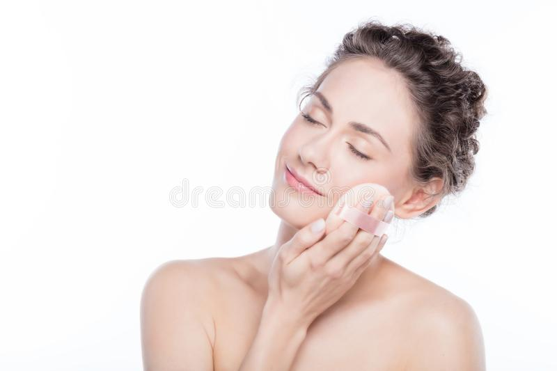 Young woman applying powder to her face. royalty free stock image