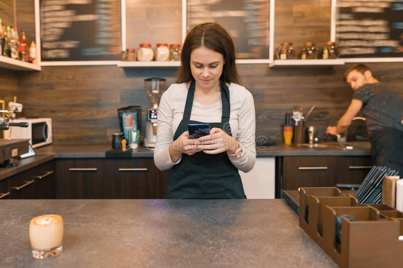 Young woman in apron coffee shop worker at bar counter, taking order on smartphone stock images