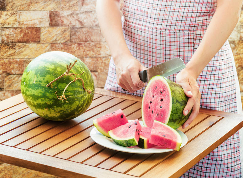 Young woman in apron slicing watermelon on wooden table royalty free stock photos