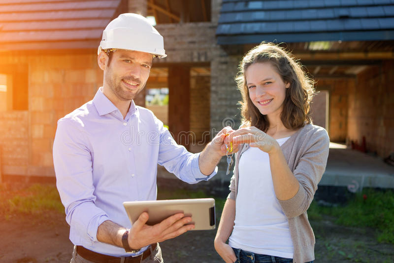 Young woman and architect on construction site royalty free stock photography
