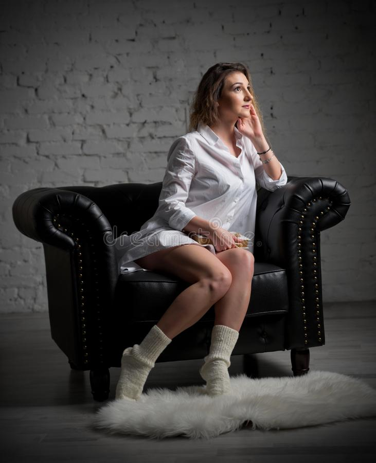 Young woman on armchair with book royalty free stock photo