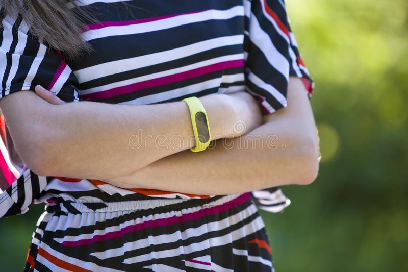 Young woman arms with fitness bracelet on outdoors blurred background.  royalty free stock photography