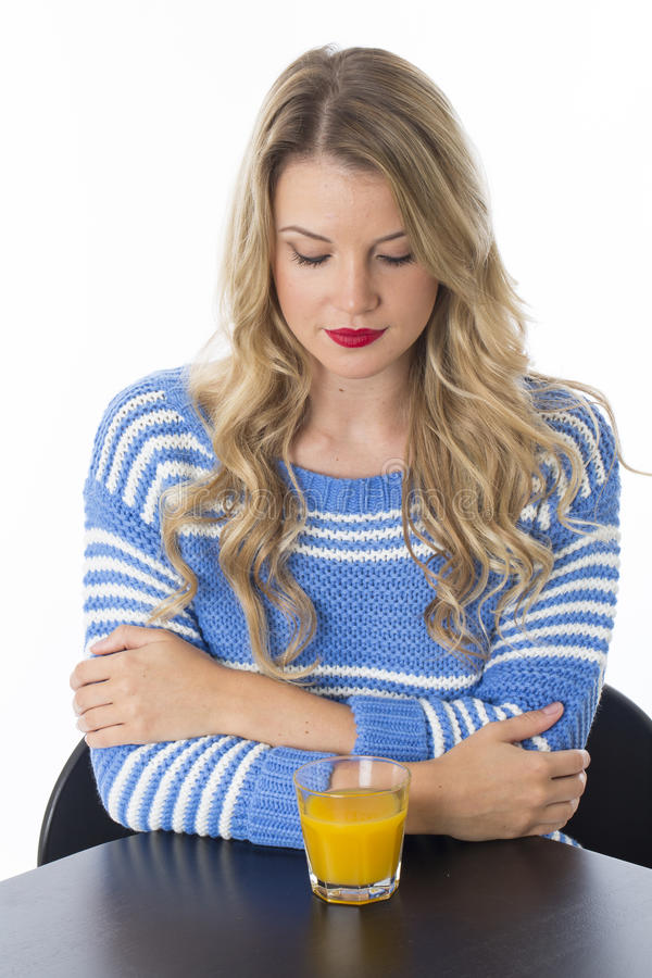 Young Woman Arms Folded with a Glass of Orange Juice Looking Down. Attractive Young Woman Arms Folded with a Glass of Orange Juice Looking Down stock image