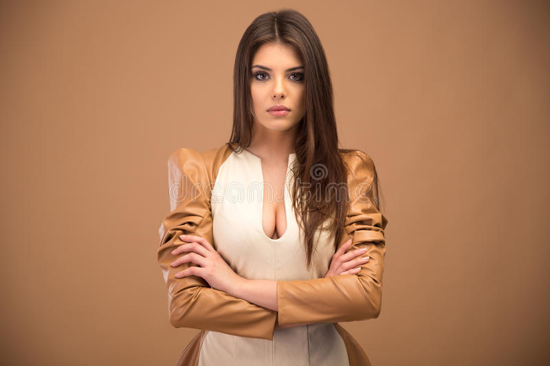 Young woman with arms folded. Portrait of attractive young woman with arms folded over brown background stock photos