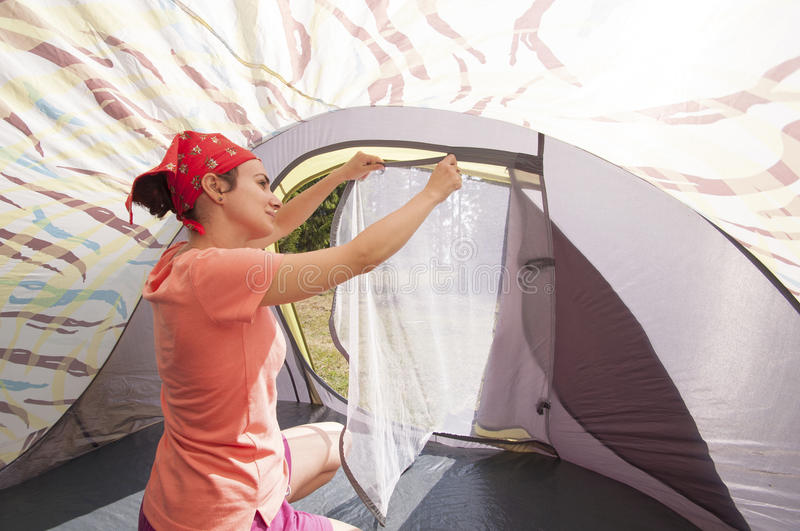 Young woman arranging the tent royalty free stock image