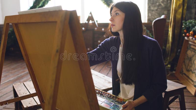 Young woman artist draw pictrure with watercolor paints and brush on easel canvas royalty free stock images