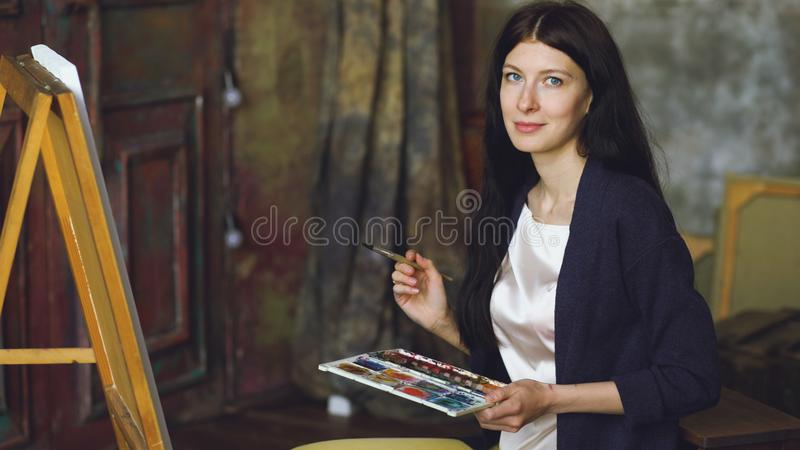 Young woman artist draw pictrure with watercolor paints and brush on easel canvas royalty free stock image