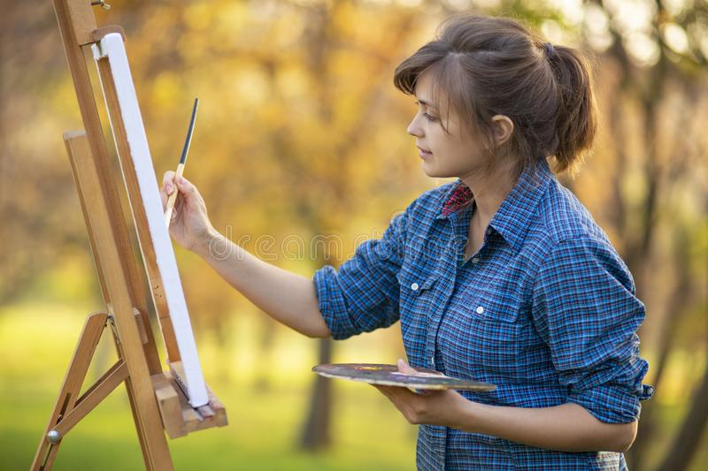 Woman artist drawing a picture on an easel in nature, a girl with a brush and a palette, a concept of creativity and a hobby royalty free stock image