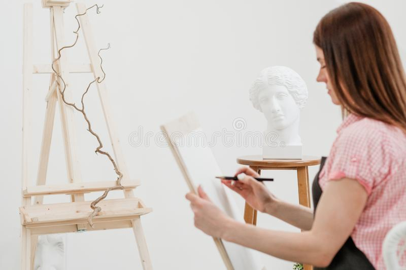 Young woman artist draws a pencil on canvas. royalty free stock photo