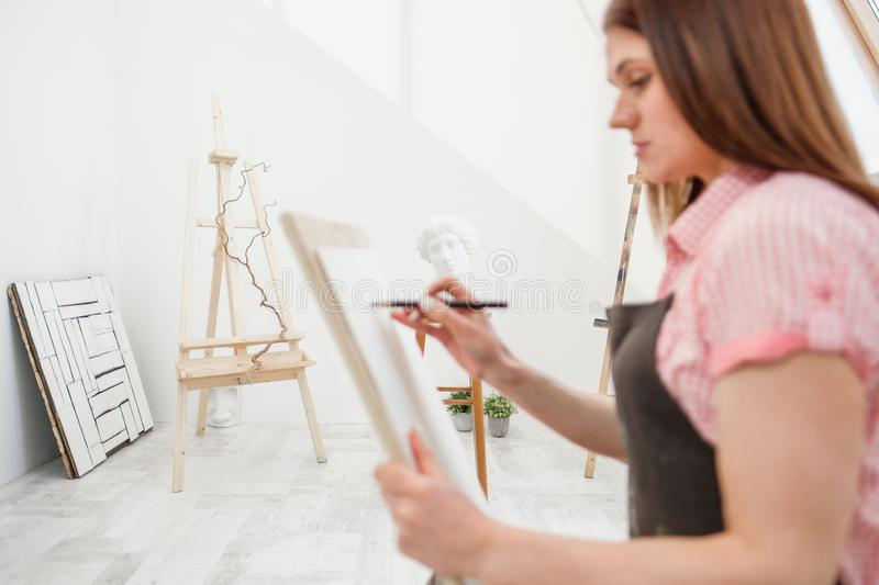 Young woman artist draws a pencil on canvas. stock images
