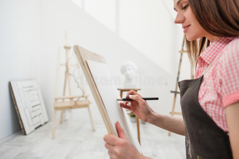 Young woman artist draws a pencil on canvas. stock photography