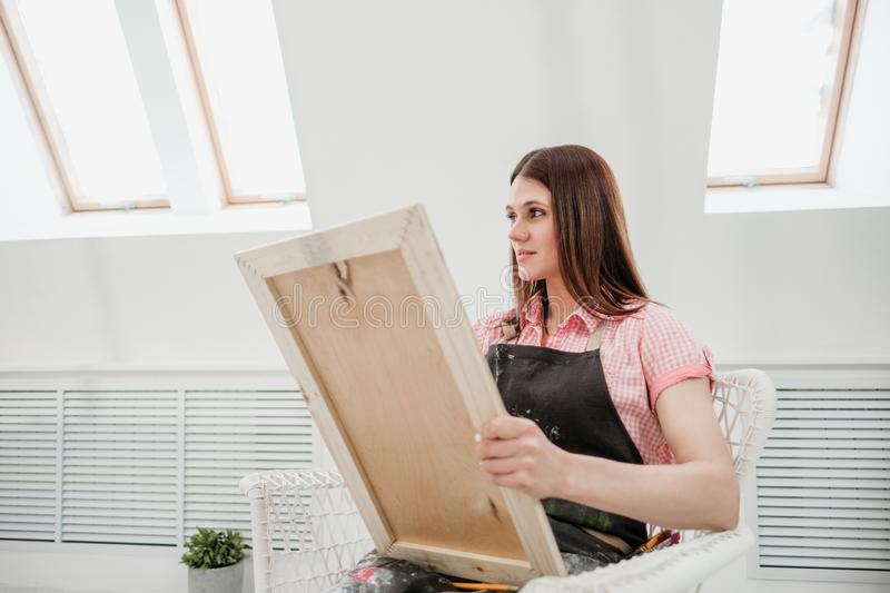 Young woman artist draws a pencil on canvas. royalty free stock photography