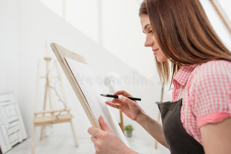 Young woman artist draws a pencil on canvas. stock image