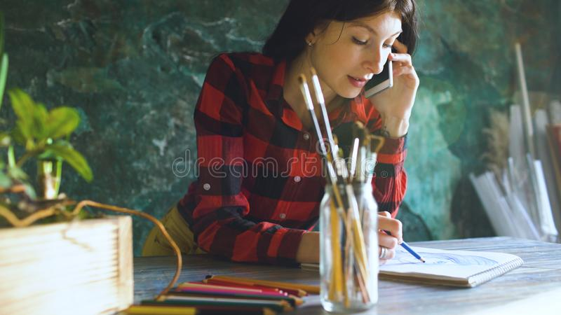Young woman artist painting scetch on paper notebook with pencil and talking phone indoors stock photography