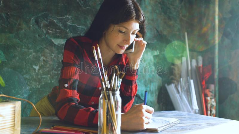 Young woman artist painting scetch on paper notebook with pencil and talking phone indoors royalty free stock images