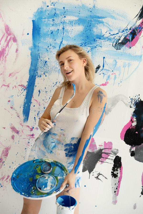 Young woman artist paints in color-stained white undershirt with blue paint, palette and brush with joy on the wall. Young woman artist paints in color-stained stock images