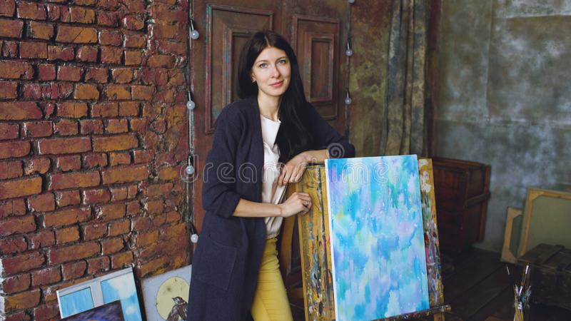 Young woman artist with watercolor paints stand near finished picture and smile into camera stock photography
