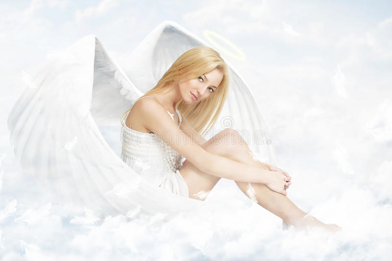 Young woman as angel sitting on clouds stock photos