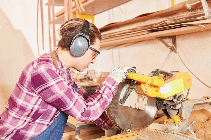 Apprentice works with wood on the chop saw. Young woman as a carpenter or joiner apprentice works with wood at the chop saw royalty free stock photos