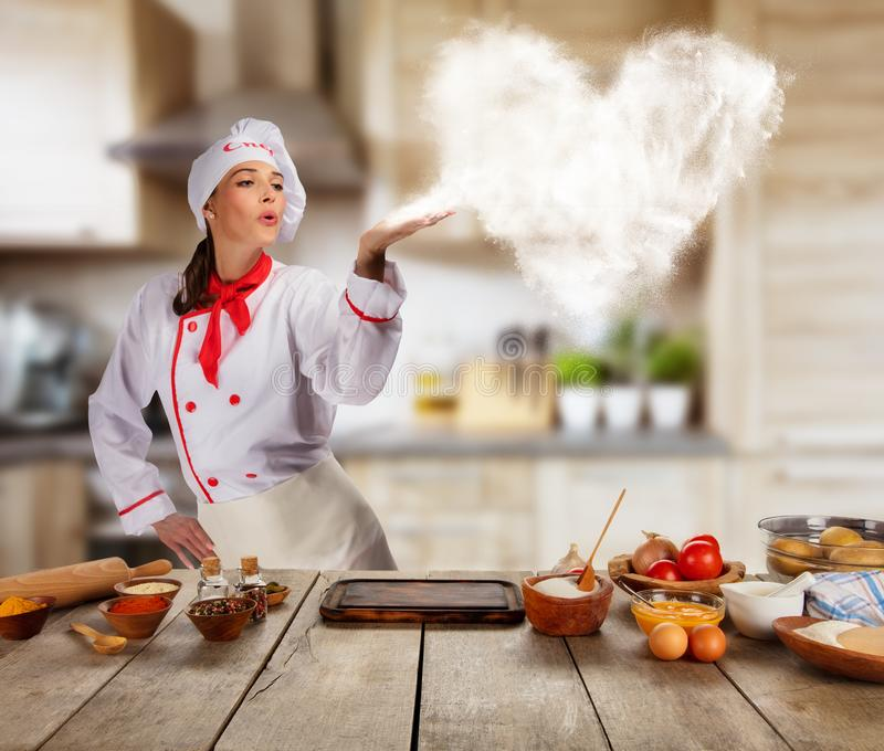 Young woman as chef in kitchen, concept of food preaparation royalty free stock photography